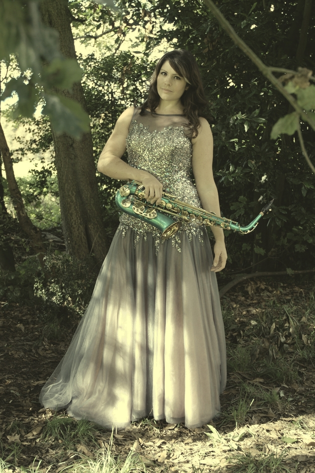 Somerset's award winning Lucy Harvey Vocalist and Saxophonist in woodland holding saxophone