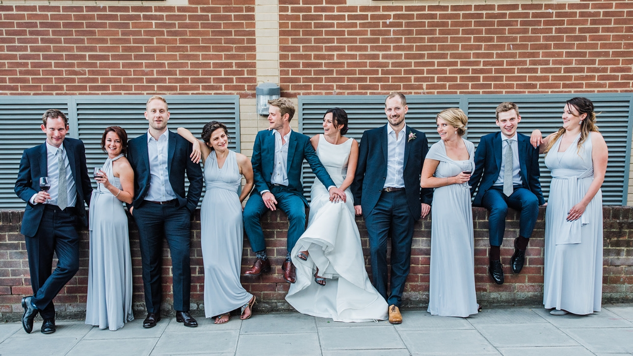 Bridal party sitting on a wall wearing multiway dresses and blue suits