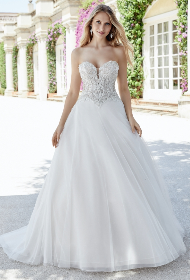 Blonde bride in wedding dress with lace bodice and full skirt.