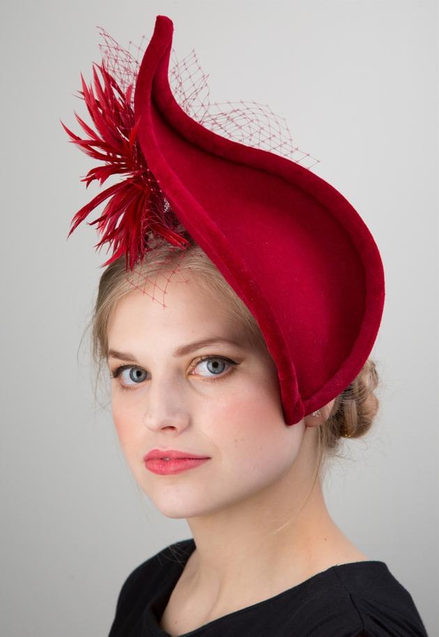 Woman wearing large red fascinator.