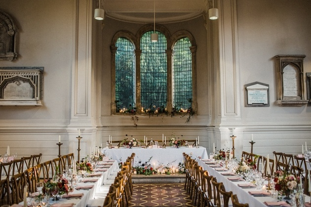 Interior of Arnos Vale wedding venue set up for wedding breakfast with flowers and candles.