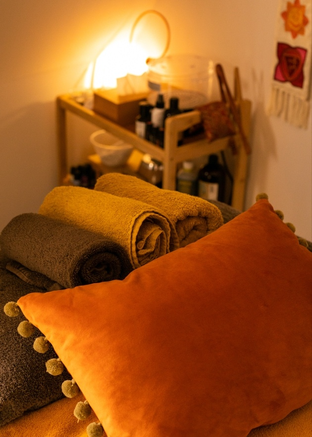 Treatment room with cushions and towels at The Kind Living Salon.