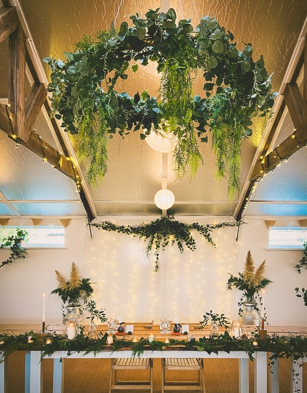 Wedding table with natural styling, foliage and hanging floral hoop.