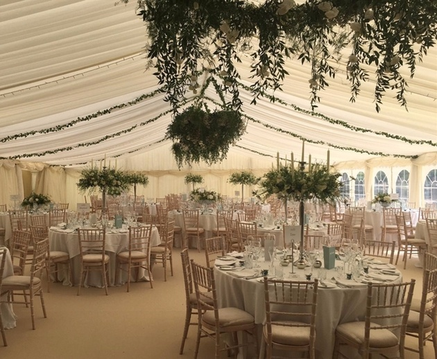 Interior of marquee dressed for a wedding with foliage and floral hoop