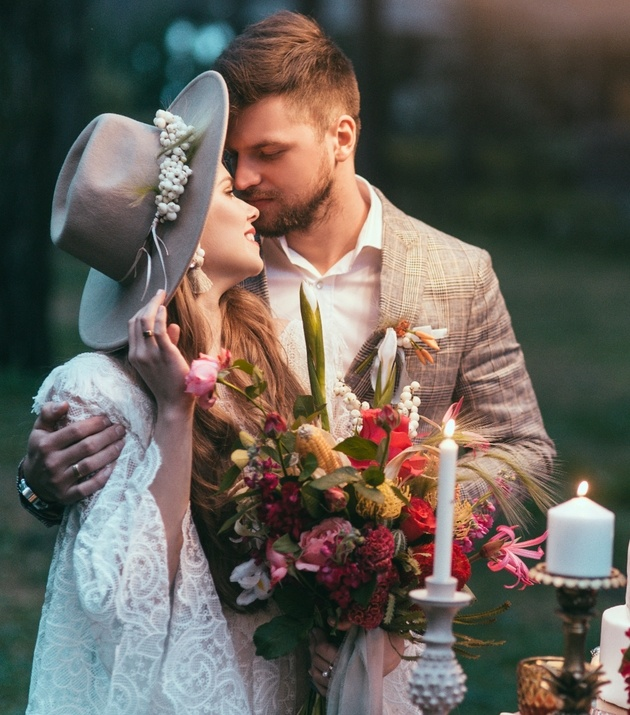Wedding couple outdoors in candlelight with bouquet and bride in fedora