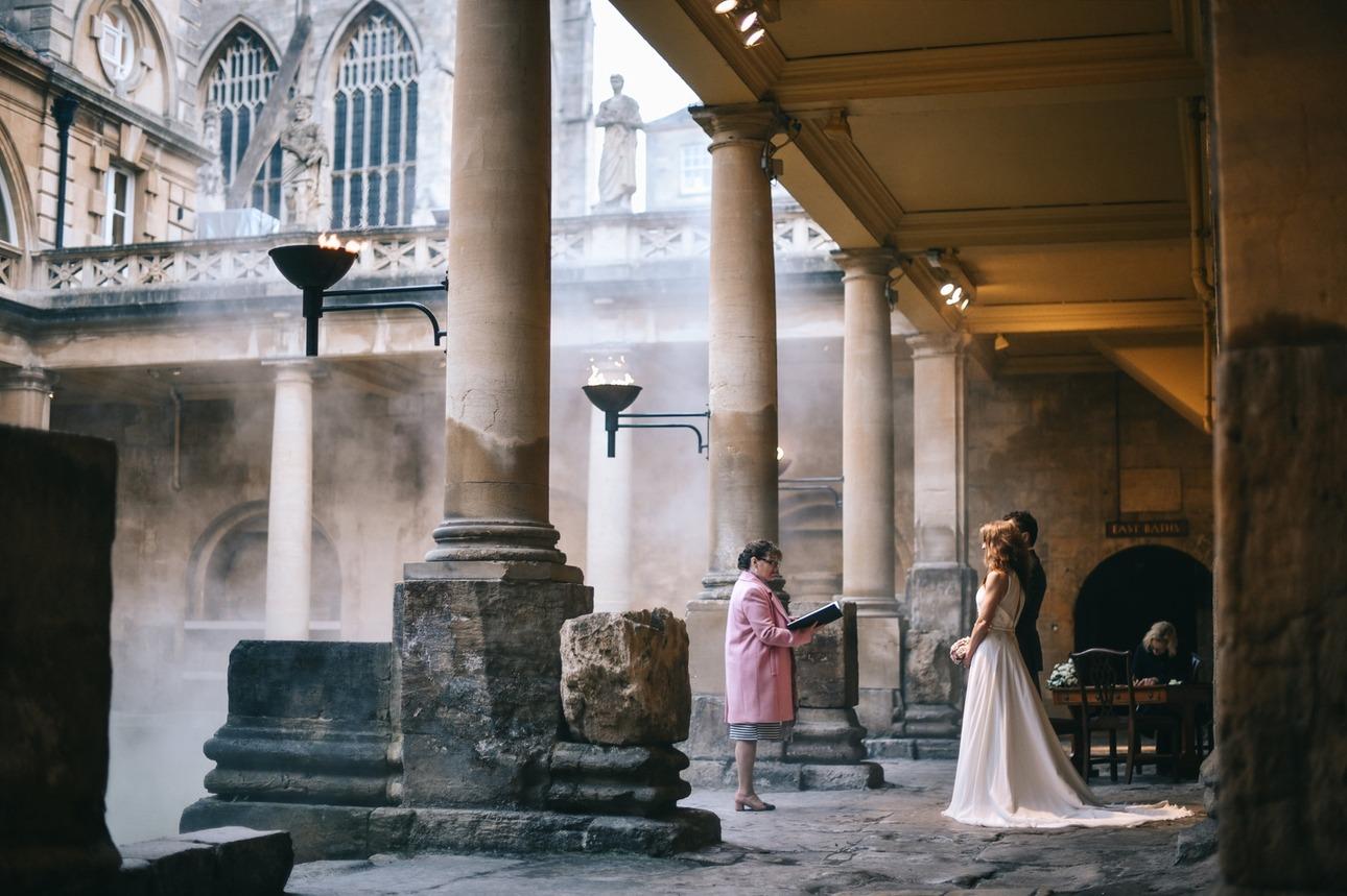 Couple having a wedding ceremony at Bath's iconic Roman Baths & Pump Room wedding venue