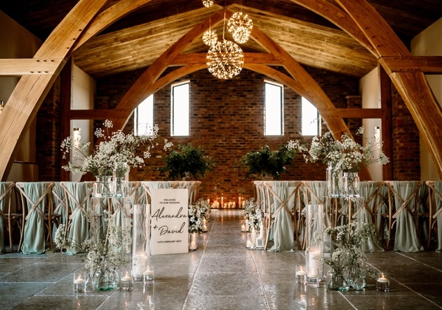 Barn venue dressed for wedding ceremony with flowers and candles