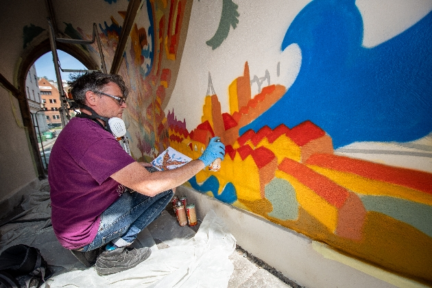 artist Andy Council painting in red roofs on the mural in the pedestrian side arches under the Church of St John on the Wall, Broad Street