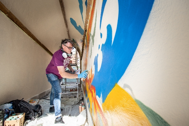 artist Andy Council working on the mural in the pedestrian side arches under the Church of St John on the Wall, Broad Street