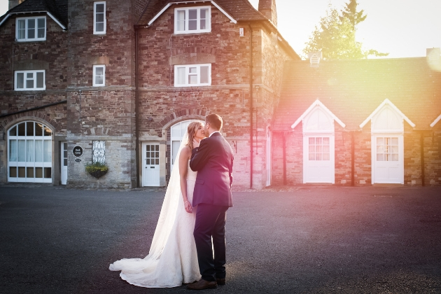 couple kissing in venue courtyard as the sun sets over the roofs