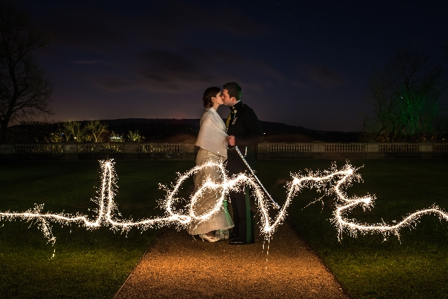 couple kissing as night falls, word love is written with a sparkler