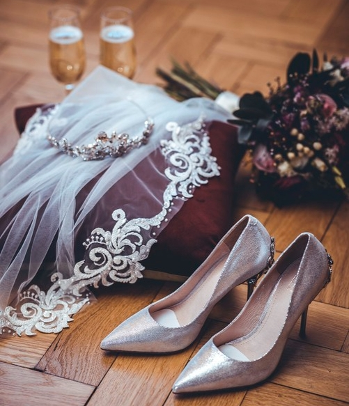 a collection of wedding accessories on a floor such as shoes tiara flowers